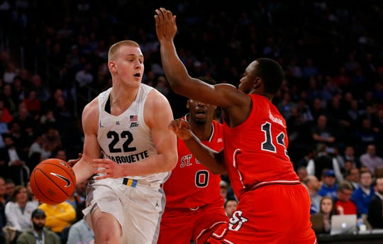 Marquette forward Joey Hauser drives against St. John's defenders during the quarterfinal of the Big East conference tournament at Madison Square Garden, March 14, 2019.