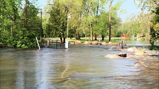 Moving water flooding the entrance to the Wesleyan Church Camp on Caine Road on Saturday, May 25, 2019.