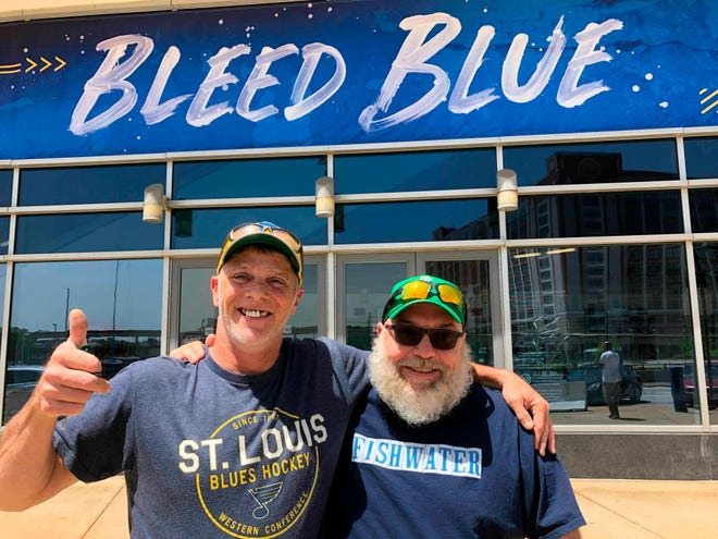 Longtime Blues fans Stanley Jackson, left, and Steven Crow stand in front of the Enterprise Center in St. Louis, a day after the Blues defeated San Jose to earn a berth in the Stanley Cup Finals.