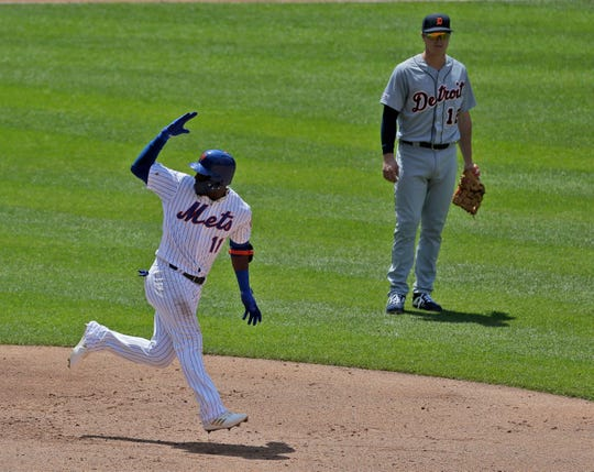 As Detroit Tigers first baseman Brandon Dixon looks on, the New York Mets' Adeiny Hechavarria reacts after hitting a three-run home run during the fourth inning.