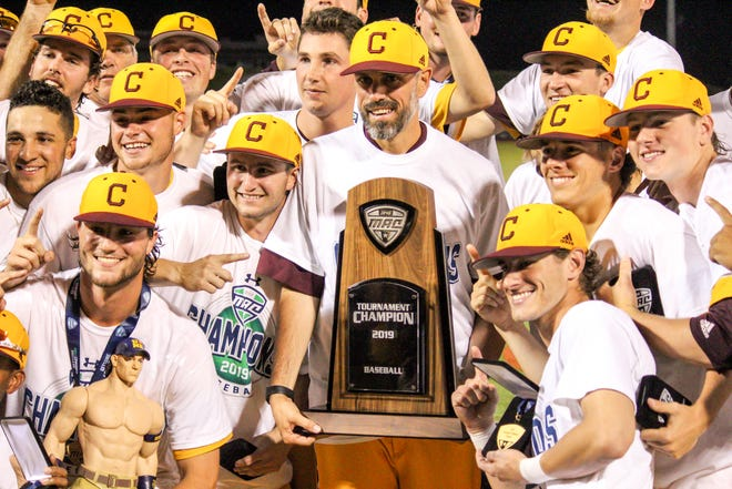Coach Jordan Bischel and his players pose for photos with the MAC championship trophy.