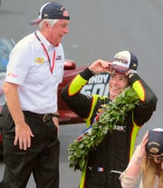Simon Pagenaud talks with owner Roger Penske as they celebrate on the Yard of Bricks after Pagenaud won the Indianapolis 500.