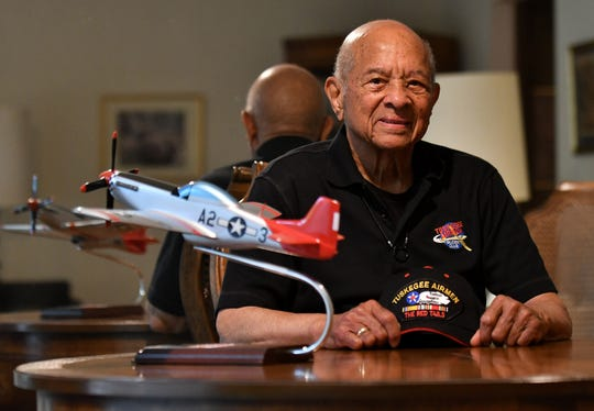 Lt. Col. Harry Stewart Jr., one of the last surviving Tuskegee Airmen, next to a model of the P-51D Mustang plane he flew in WWII.