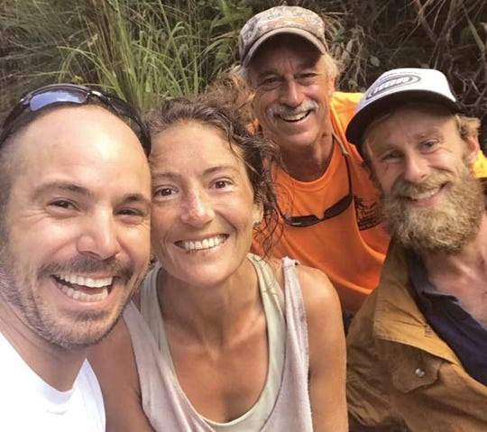 Amanda Eller, second from left, poses for a photo Friday after being found by searchers, Javier Cantellops, far left,  Troy Jeffrey Helmer and Chris Berquist above the Kailua reservoir in East Maui, Hawaii.