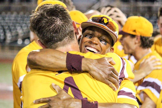 Outfielder David Cole, right, hugs catcher Blake Cleveland after Central Michigan won the MAC championship on Saturday night.