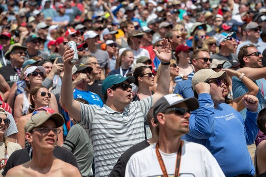 Fans react as Simon Pagenaud (22), of Team Penske, pass after the restart to get into first place during the 103rd running of the Indianapolis 500 on Sunday, May 26, 2019.