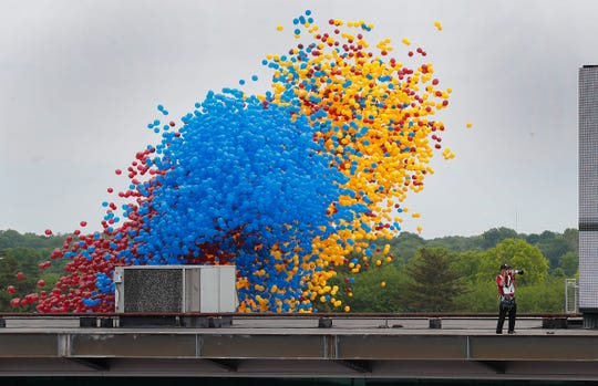 IMS photographer Chris Jones stands on the top of the media center as the balloons are released behind him before the start of the Indianapolis 500 at Indianapolis Motor Speedway on Sunday, May 26, 2019.