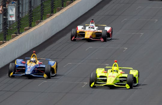 The top-three finishers, Simon Pagenaud (22) of Team Penske, Alexander Rossi (27) of Andretti Autosport and Takuma Sato (30) of Rahal Letterman Lanigan Racing head into turn one on the white flag lap during the 103rd running of the Indianapolis 500, Sunday, May 26, 2019, in Speedway, Ind. Simon Pagenaud (22) of Team Penske won the race.