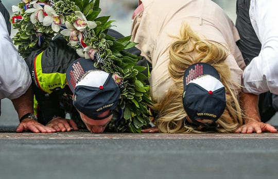 Simon Pagenaud (22) and fiancee Hailey McDermott kiss the bricks after Pagenaud won the 103rd running of the Indy 500 at Indianapolis Motor Speedway, Sunday, May 26, 2019.