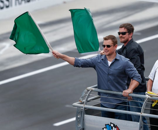 Actors Matt Damon and Christian Bale wave the green flags to start the 103rd Indianapolis 500 at Indianapolis Motor Speedway on May 26, 2019.