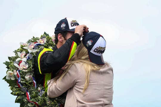 Simon Pagenaud (22) and fiancee Hailey McDermott sneak a kiss after Pagenaud won the 103rd running of the Indy 500 at Indianapolis Motor Speedway, Sunday, May 26, 2019.