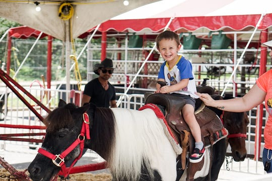 Adam Theriot enjoys a petting zoo at the Cajun Heartland State Fair Saturday, May 25, 2019.
