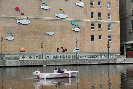 Michael Medcalf of Retro Boats MKE takes Journal Sentinel reporter Grace Connatser out for a boat driving lesson before she took over the helm. Retro Boat MKE rents out classic boats from the 1950s converted to run on battery power on the Milwaukee River.  They dock at 104 E. Mason St. on the Milwaukee River.  The boats seat up to five people.  Retro Boat MKE also rents  donut boats that can seat up to 10.