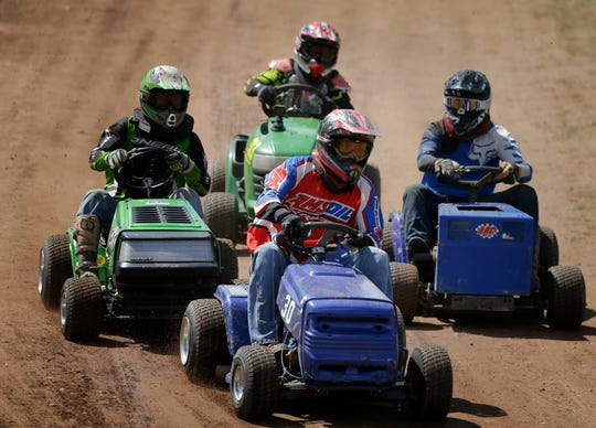Racers are bunched up going into the first turn during the season-opening races of the Wisconsin Lawn Mower Racing Association on Sunday in Fifield, Wis.