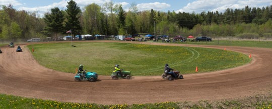 Racers round the first turn during the season-opening races for the Wisconsin Lawn Mower Racing Association Sunday.