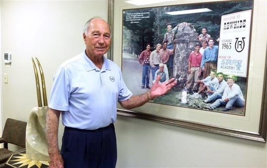 Bart Starr points out a picture of Rawhide Boys Camp, one of his favorite charities, at his office in Birmingham, Alabama.