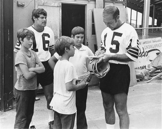 Bart Starr signs autographs before his last practice as a Packer in July 1972. Looking on is Scott Hunter, who took over as quarterback.