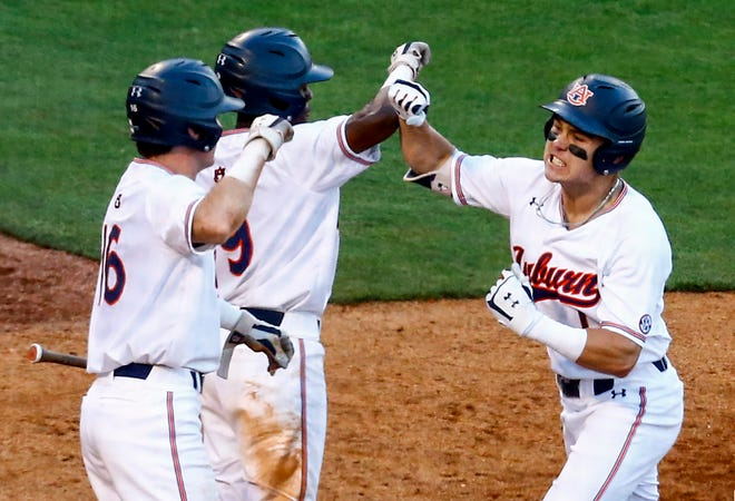 Auburn's Judd Ward (1) celebrates with teammates Ryan Bliss (9) and Kason Howell (16) after hitting a two-run home run against Tennessee in the SEC Tournament on Tuesday, May 21, 2019, in Birmingham, Ala.