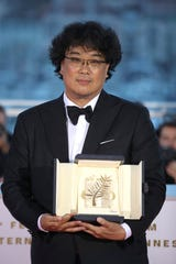 Director Bong Joon-ho poses with the Palme d'Or award for the film 'Parasite' during a photo call following the awards ceremony at the 72nd international film festival, Cannes, southern France, Saturday, May 25, 2019.