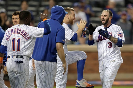 New York Mets' Tomas Nido, right, celebrates with teammates after hitting a walk-off solo home run off Detroit Tigers relief pitcher Buck Farmer during the 13th inning of a game Saturday, May 25, 2019, in New York. The Mets won 5-4.