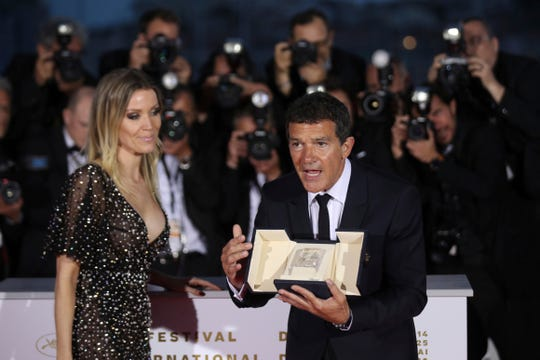 Actor Antonio Banderas, right, holds the best actor Palme d'Or award for the film 'Pain and Glory' as he poses with Nicole Kimpel during a photo call following the awards ceremony at the 72nd international film festival, Cannes, southern France, Saturday, May 25, 2019.