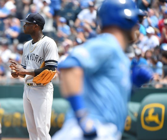 New York Yankees starting pitcher Domingo German, left, looks at the scoreboard after giving up a home run to Kansas City Royals' Ryan O'Hearn in the fourth inning during a game Sunday, May 26, 2019, in Kansas City, Mo.