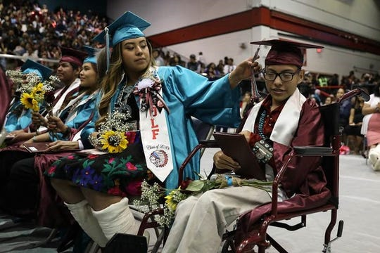 Shiprock High School graduate Angel Wolf adjusts the tassel of classmate Elias Varela during the commencement exercises on Friday at the Chieftain Pit.