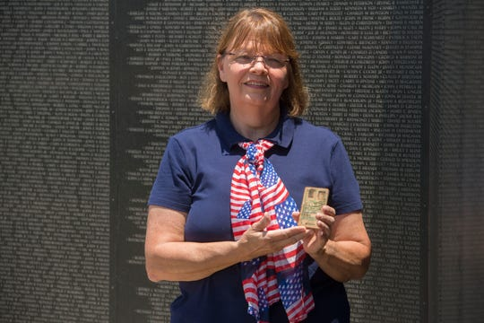 Jill Hubbs holds the military ID of an American pilot who was shot down and killed in 1965. Hubbs, a Pensacola filmmaker, found the ID while visiting a rural Vietnamese province late last year.