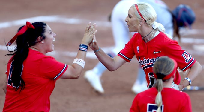 Arizona's Taylor McQuillin, (18) left, comes out of the dugout to congratulate starter Alyssa Denham (22) after she pitched out of a bases loaded no out jam against Mississippi in the second inning of Game 2 of the NCAA Super Regional at Hillenbrand Stadium, Saturday, May 25, 2019, Tucson, Ariz.