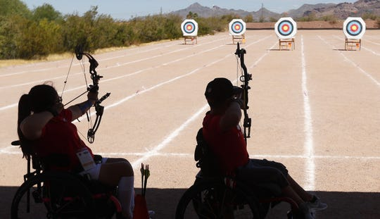 Olivia Curcuru, 13, (L) and Gabriel Castillo, 14, shoot arrows during The Desert Challenge Games at Papago Park Archery Range in Phoenix, Ariz. on May 26, 2019. The pair have been shooting together for practice.