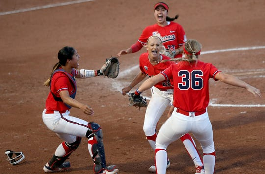Arizona players rush the circle and starter Alyssa Denham (22) after the final out in a 9-1 win against Mississippi in Game 2 of the NCAA Super Regional at Hillenbrand Stadium, Saturday, May 25, 2019, Tucson, Ariz.