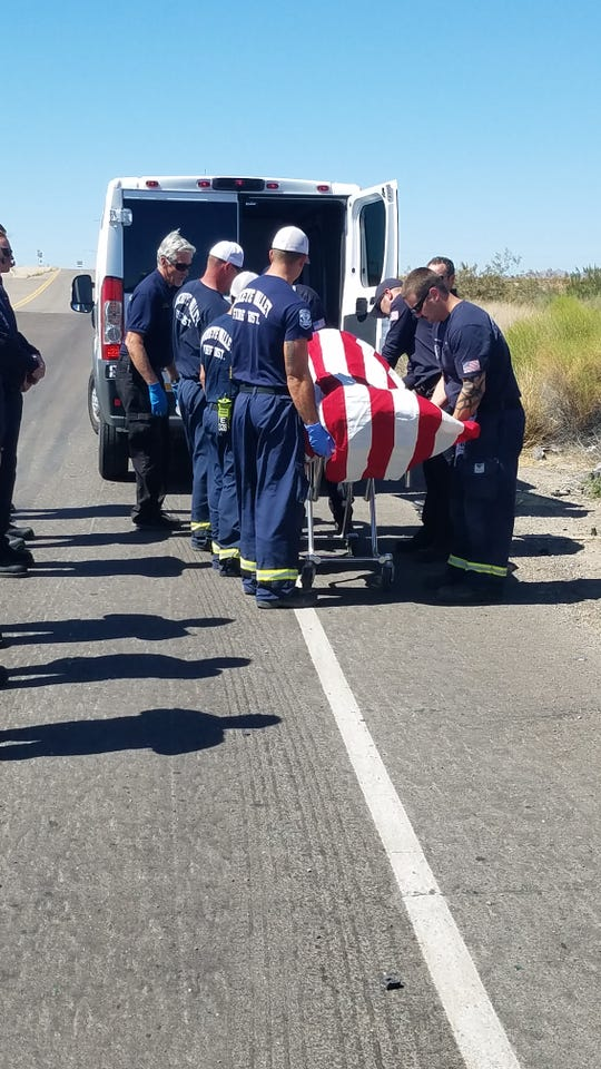 Public safety personnel escort the body of Eric Merrill, who spent 40 years in fire service, to the downtown Phoenix medical examiner's office.
