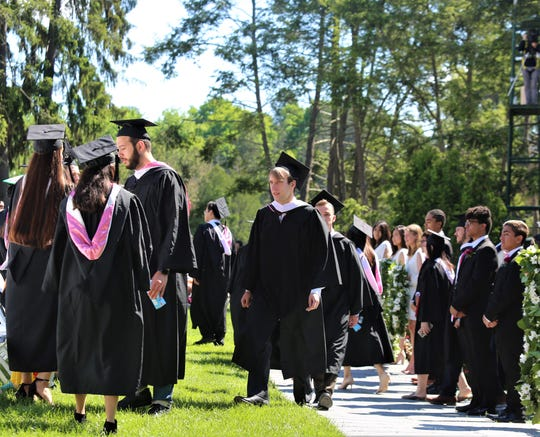 Walter Alexander (center) walks with his fellow classmates toward their seats ahead of the 2019 Vassar College graduation ceremony on Sunday, May 26, 2019.