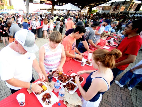 Festivalgoers eat crawfish at the 2019 Mudbug Madness in downtown Shreveport.