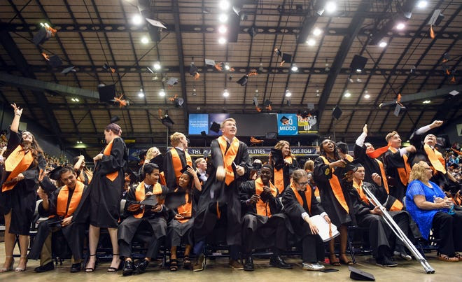 Students from Washington High School toss their caps after graduating Sunday afternoon, May 26, at the Sioux Falls Arena.