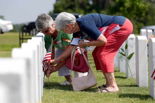 Visitors at the Tallahassee National Cemetery place flags at last year's Memorial Day program. NCA is not hosting public events for Memorial Day this year, including the mass placement of gravesite flags.