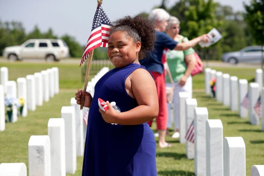 Aaliyah Phillips, 9, carries American flags to place at the grave-sites of veterans. The Tallahassee National Cemetery hosts a Memorial Day Program for the community to come and honor the veterans who have been laid to rest Sunday, May 26, 2019.