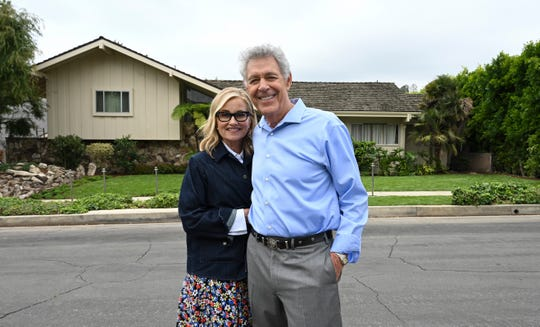 "Maureen McCormick, left, and Barry Williams, who played the oldest children on ""The Brady Bunch,"" stand across the street from the home that served as the exterior for the beloved family sitcom, which ran on ABC from 1969 to 1974."