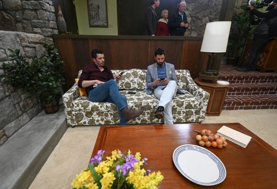 """Property Brothers"" stars Jonathan Scott, left, and his twin brother, Drew, sit on the couch in the living room they helped design and build as  part of a re-creation of ""The Brady Bunch"" house for HGTV's ""A Very Brady Renovation."""