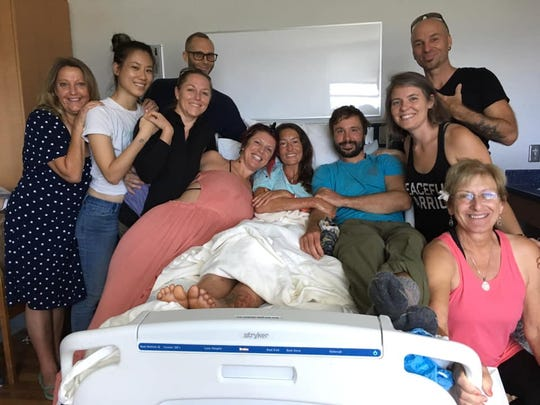 This photo provided by Sarah Haynes shows hiker Amanda Eller, center, in her hospital bed surrounded by friends and family after she survived on wild fruit, water and grit after being lost for 17 days in the Hawaiian forest.