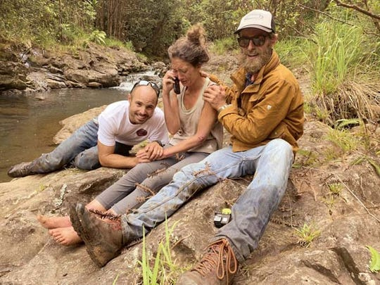 In this Friday, May 24, 2019, photo provided by Troy Jeffrey Helmer, shows Amanda Eller, second from left, after being found by searchers, Javier Cantellops, far left, and Chris Berquist, right, above the Kailua reservoir in East Maui, Hawaii, on Friday afternoon. The men spotted Eller from a helicopter and went down to retrieve her. She was taken to the hospital and was in good spirits, her family said. Eller had been missing since May 8.