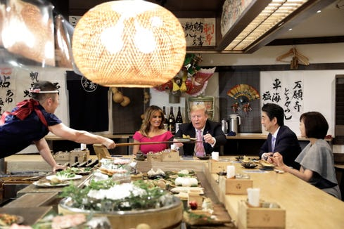 U.S. President Donald Trump is served a baked potato while sitting at a counter with US First Lady Melania Trump, Shinzo Abe, Japan's prime minister and Akie Abe, wife of Shinzo Abe, during a dinner at the Inakaya restaurant in the Roppongi district of Tokyo on May 26, 2019.
