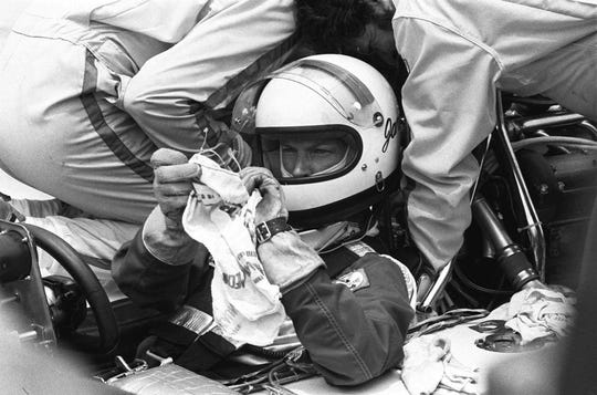 Janet Guthrie wipes her glasses as her pit crew looks at her car during the 61st Indy 500 on May 29, 1977.