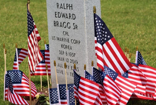 "The family of Ralph Edward Bragg Sr. decorated his headstone, newly arrived at Texas Veterans Cemetery at Abilene, with more than two dozen flags. Bragg moved from West Virginia to Abilene, dying just two months ago. His daughter, Jennifer Evans, and her husband, Ben, and other family members had hoped it would arrive by Father's Day but were delighted to see it for Memorial Day. The inscription ""All my exes live in Texas"" is a reference to the George Strait hit song; Evans said her father claimed to have had five ex-wives in the state, which is why he resided in West Virginia and not West Texas."