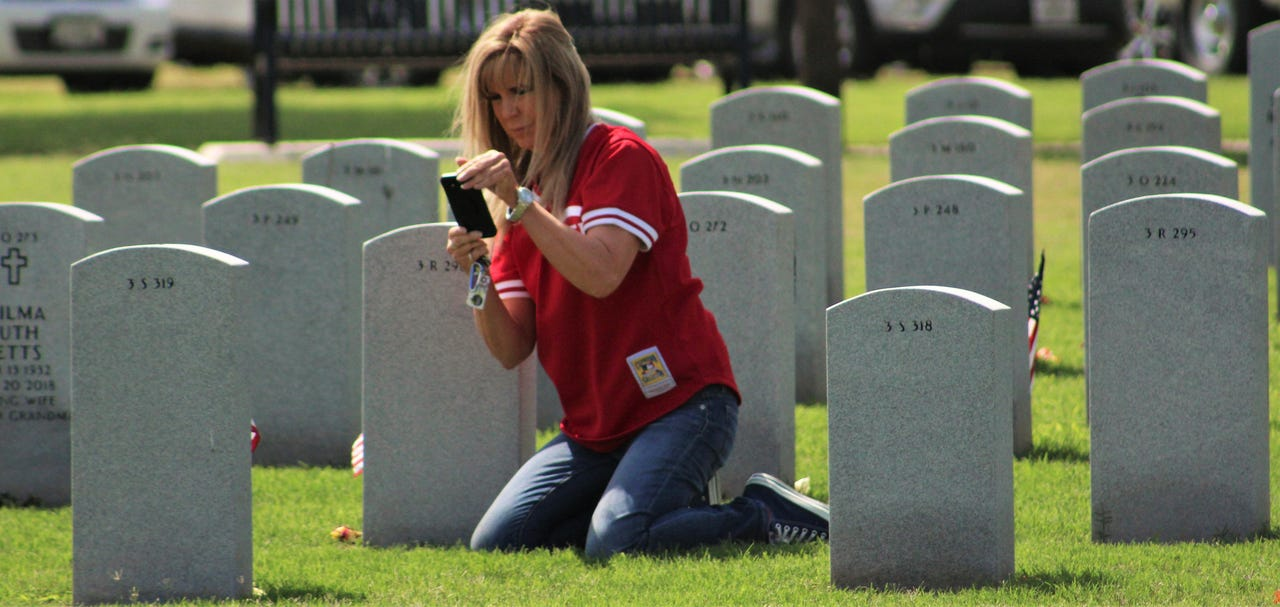 Sharon Miller on Monday photographs a headstone of a cousin's best friend. Capt. Jeffrey Walter Welch. He died in 2018, and family living elsewhere has not seen his headstone at Texas State Veterans Cemetery at Abilene. May 27, 2019