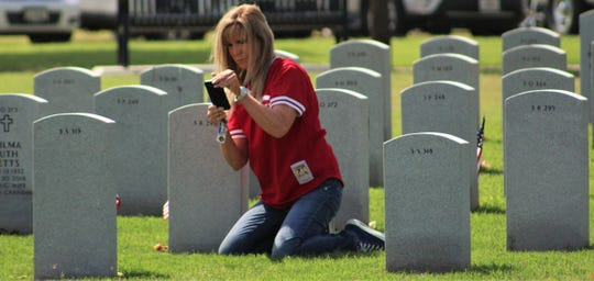 Sharon Miller on May 27 photographs a headstone of a cousin's best friend. Capt. Jeffrey Walter Welch. He died in 2018, and family living elsewhere has not seen his headstone at Texas State Veterans Cemetery at Abilene.