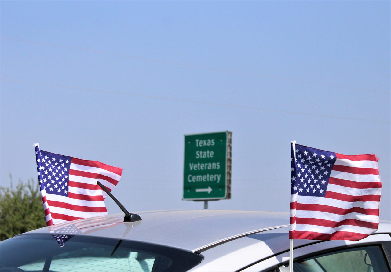 U.S. flags attached to a vehicle flap in a brisk southerly wind Monday at the entrance Texas State Veterans Cemetery at Abilene. Attendees had to park on both sides of FM 600 to the south and north of the cemetery. May 27, 2019