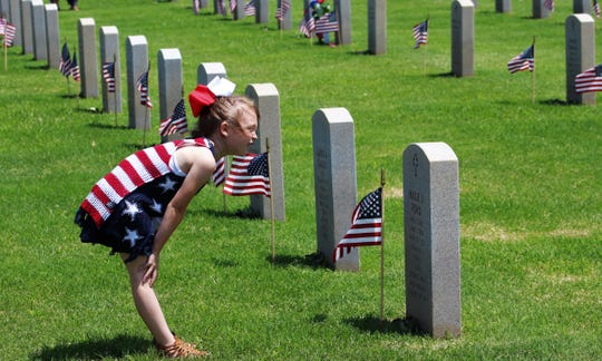 Adilynn Poteet, 6, reads the inscription on a headstone after the May 27 Memorial Day ceremony at Texas State Veterans Cemetery at Abilene.