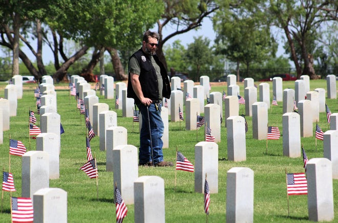 Will Holloway of Clyde, who put in 20 years in the Air Force, walked quietly by himself among the headstones at Texas State Veterans Cemetery at Abilene at a Memorial Day observance was starting Monday.