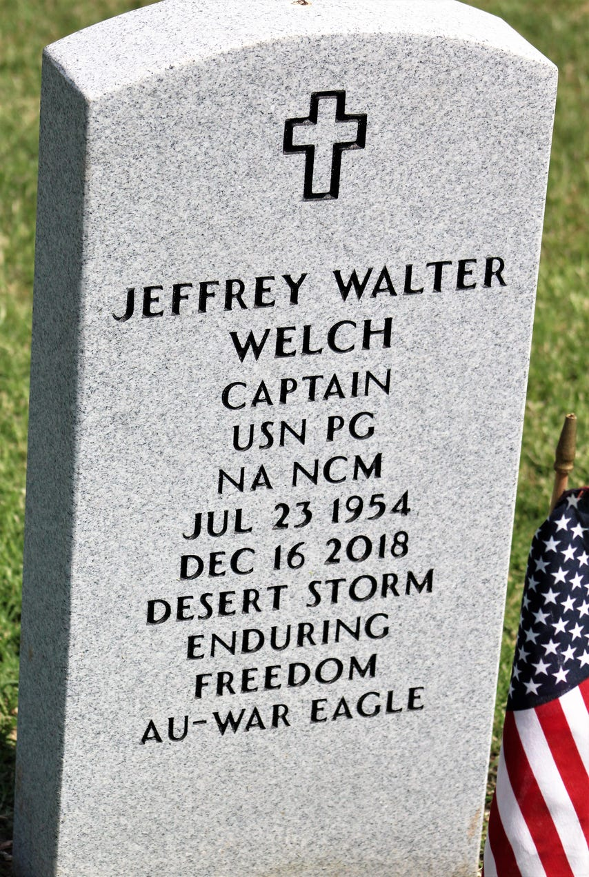 The headstone of a Navy veteran, decorated with a flag.